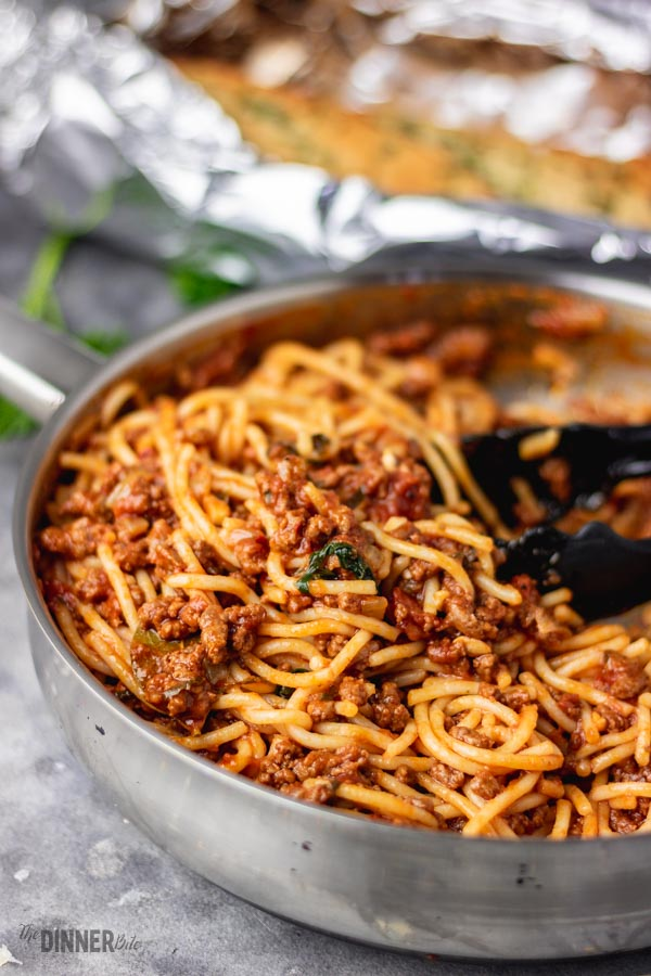 spaghetti and tomato beef sauce in a skillet.