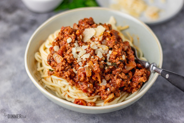 Bolognese sauce served over cooked spaghetti.