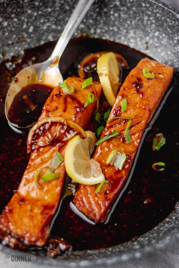 honey garlic salmon in a skillet with a spoon and some lemon slices.