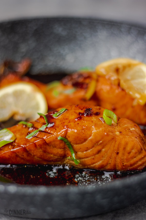 a close shot of honey garlic salmon in a frying pan.