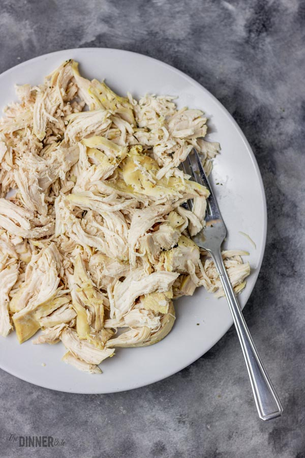 shredded chicken in a white bowl.