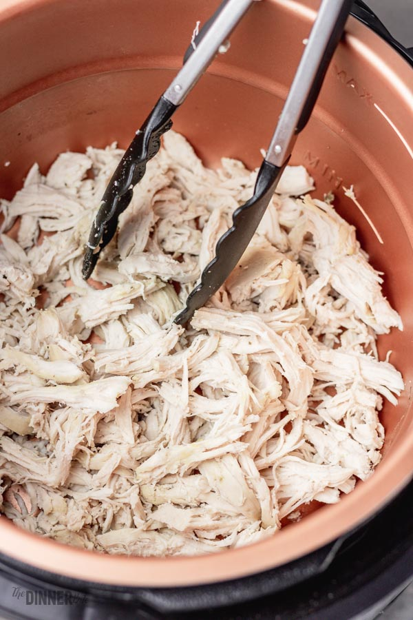 Shredded chicken in a pressure cooker with a thong.