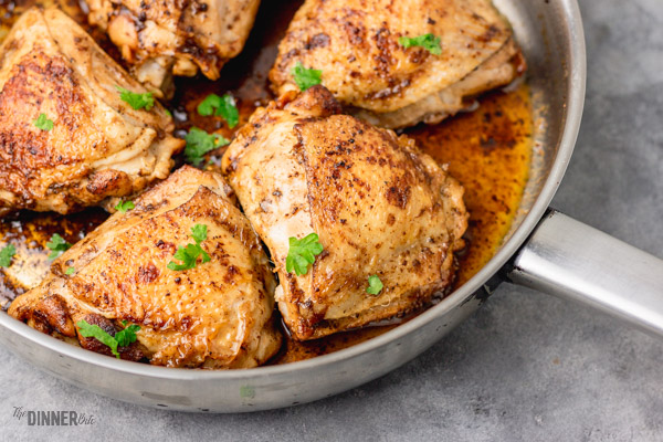 pan seared chicken thighs in an iron skillet.