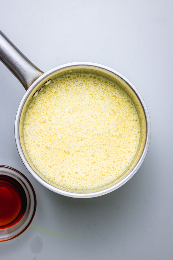 freshly boiled turmeric milk with frothy topping in a saucepan.