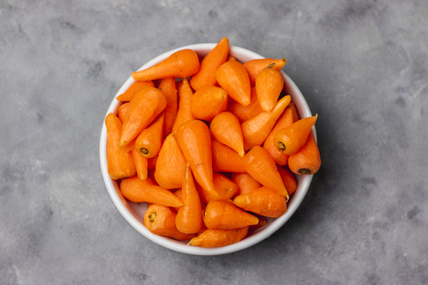 peeled and cleaned carrots in a white bowl.