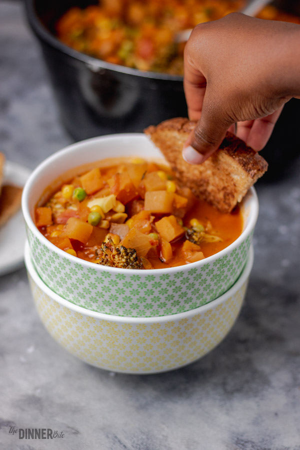 toast dipped in a bowl of vegetable soup.