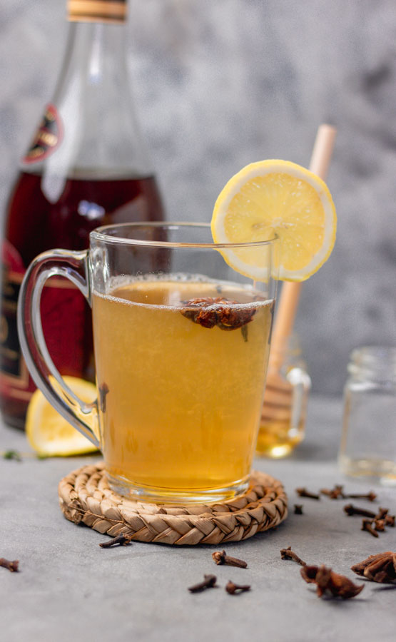 easy hot toddy in a clear mug with star anise and cloves and a slice of lemon.