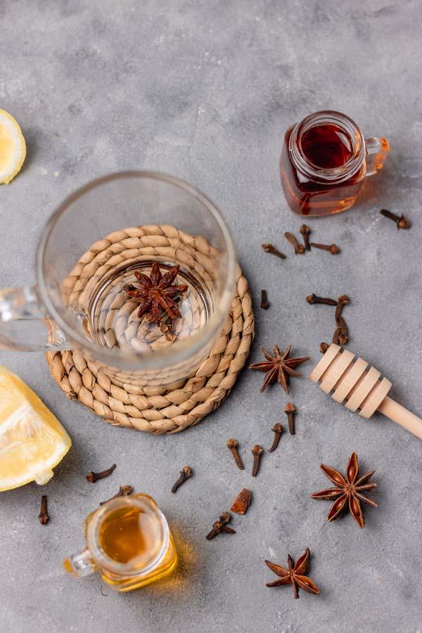 A mug, whiskey, honey, cloves, lemon , star anise and honey stirrer for hot hot toddy.