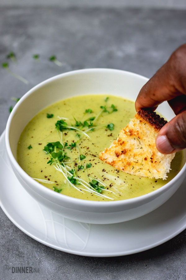 a hand of a man dipping crusty bread into broccoli soup.