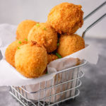 fried mashed potato balls in a basket.