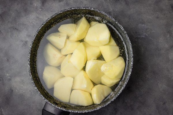 potatoes in a pan coveved with cold water about to be boiled.