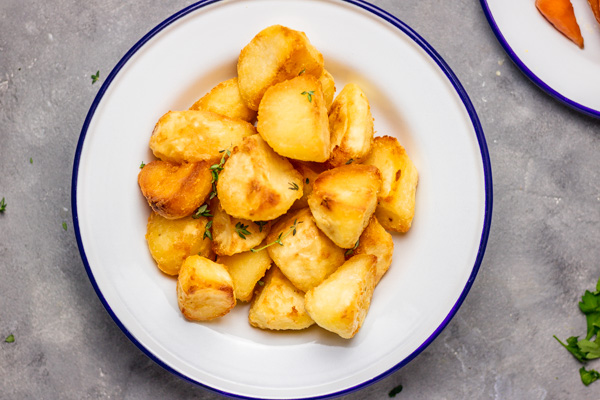 overhead shot of perfect roast potatoes in a white plate.