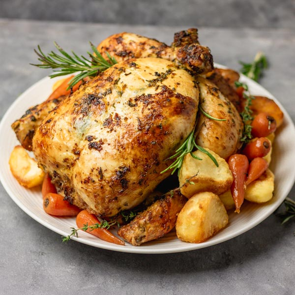 simple roast chicken dressed with glazed carrots and crunchy roast potatoes.