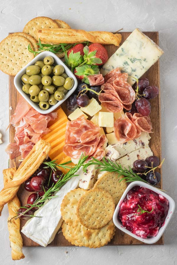 Cheese plate with cheeses, olives, fruits and dips.