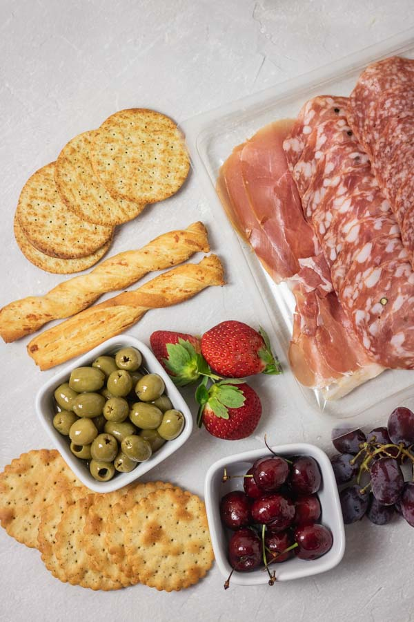 cured meats, crackers, olive and fruits for cheese board.