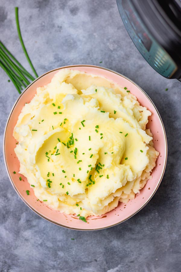 instant pot mashed potatoes in a pink bowl. mashed potatoes garnished with chopped chives and melted butter