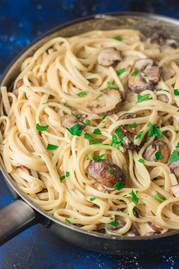creamy mushroom pasta in a skillet garnished with parsley.