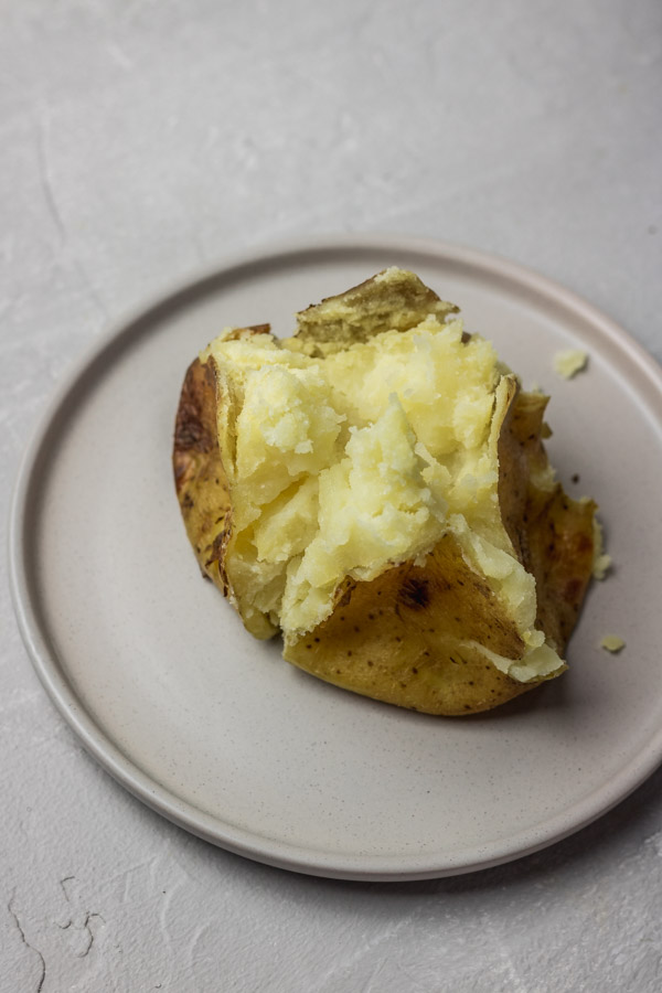 Instant pot baked potatoes in a flat plate.