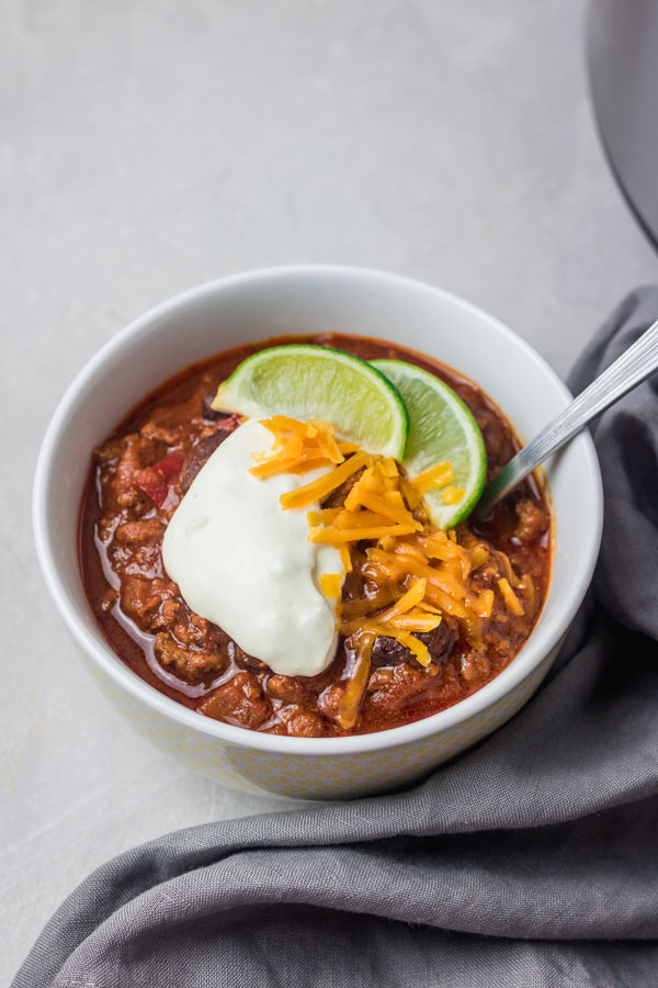 instant pot chilli garnised with sour cream, cheese and lime wedge.