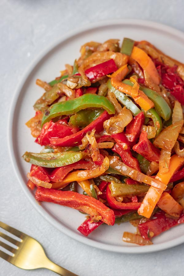 a plate of sauteed peppers made with red, green and orange bell peppers.