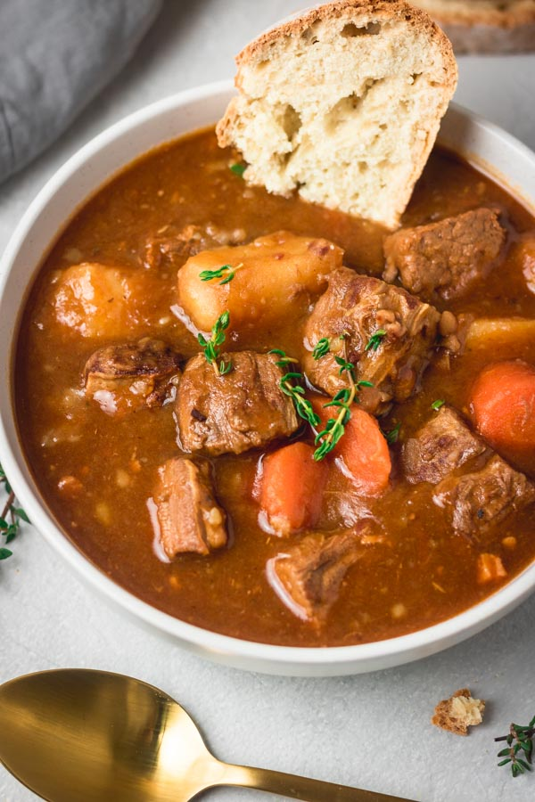 a bowl of instant pot Guinness beef stew and a side of Irish soda bread.
