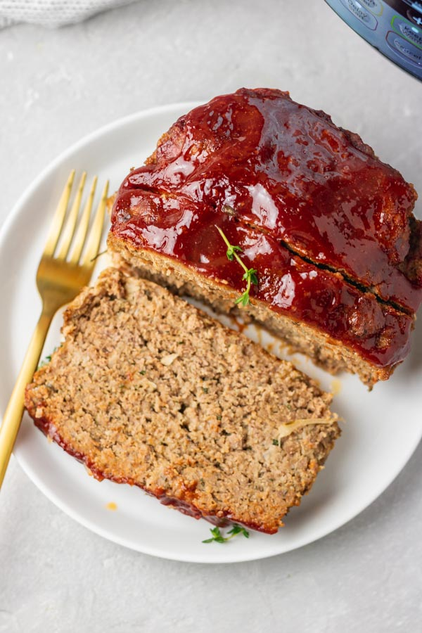 a plate of a meatloaf and a gold fork with an instant pot on the side.