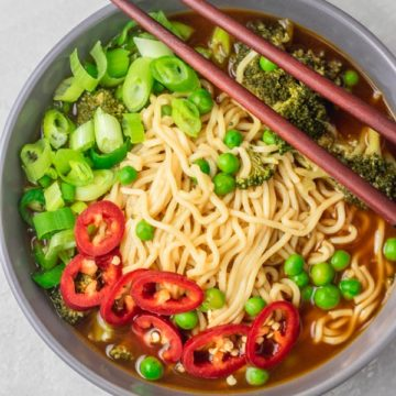a bowl of instant pot ramen noodles topped with chopped green onions and jalapeno.