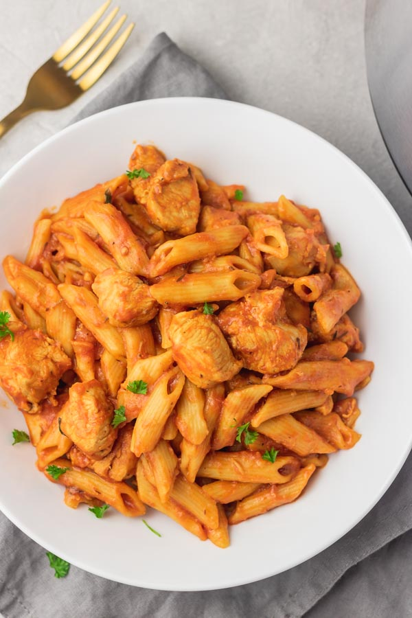 a plate of pasta and chicken in tomato sauce.