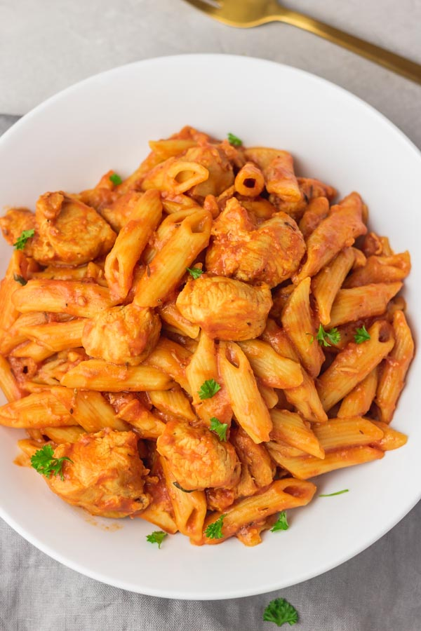 a plate of chicken and pasta in tomato sauce and a fork.