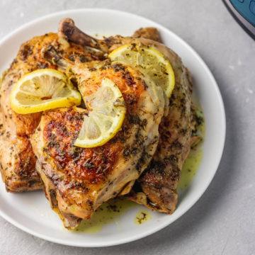 three lem garlic chicken legs with lemon slices on a plate.