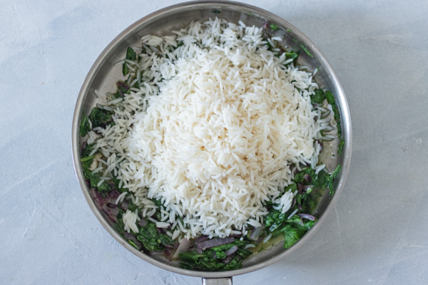 mixing white rice with cooked spinach.