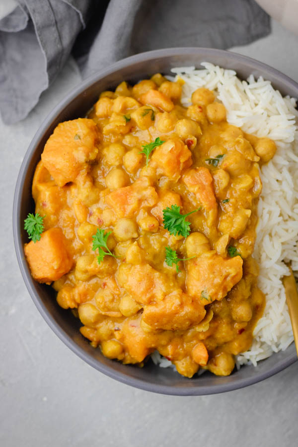 sweet potato and chickpea curry served in a grey bowl with basmati rice.