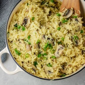 a pot of mushroom rice pilaf garnised with chopped green onions.