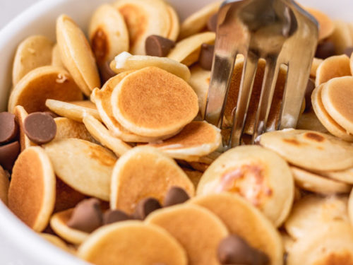 A BOWL OF CEREAL PANCAKE WITH CHIC CHOCS.