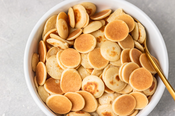 a bowl of cereal pancake with a golden spoon.