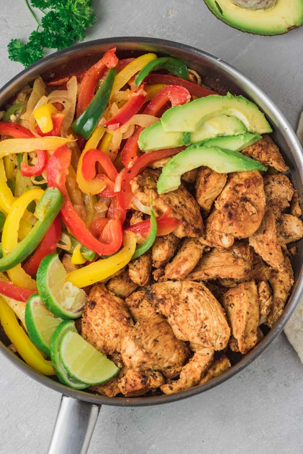 a skillet full of chicken breast pieces and sauteed peppers and onions with avocado slices.