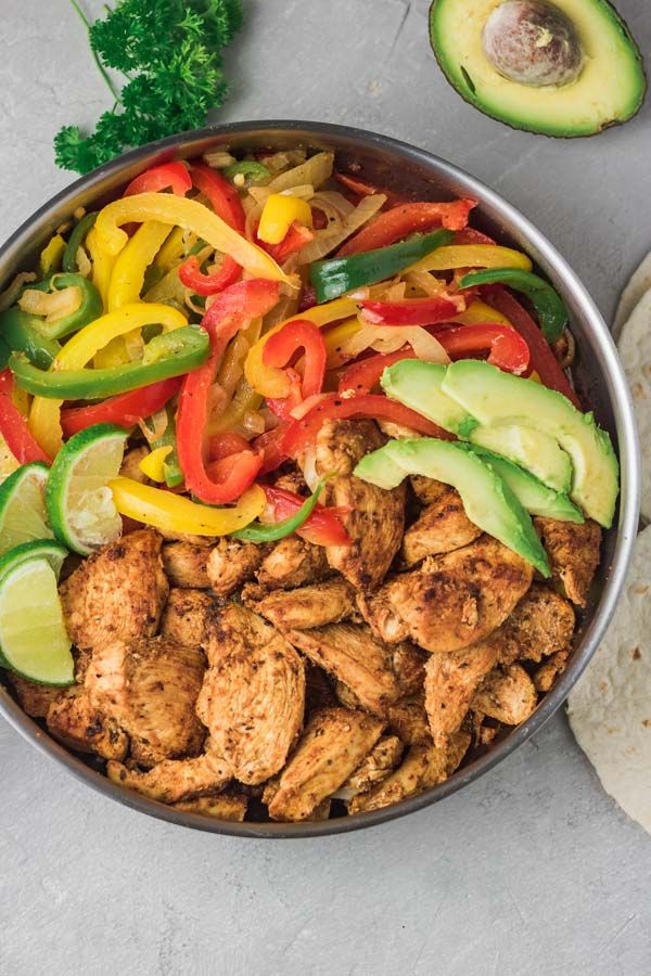 a pan of cooked chicken and peppers.