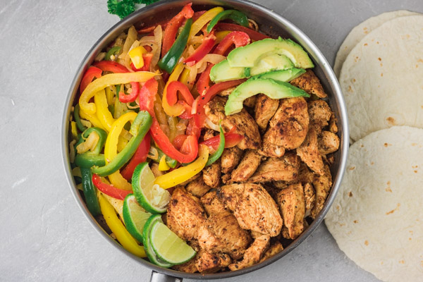 a skillet of chicken fajitas and tortilla wraps on the side.