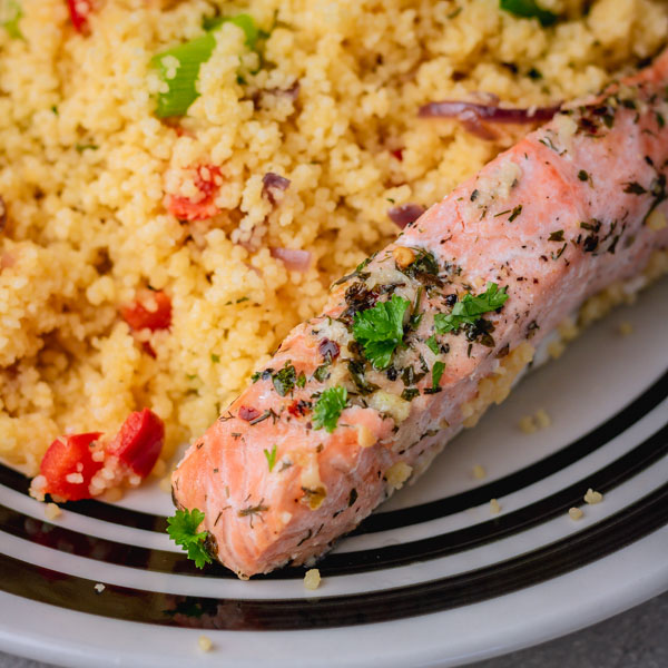a plate of vegetable couscous and baked salmon fillet garnished with chopped parsley.