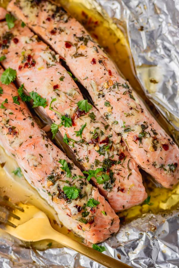 three fleshly baked salmon in a foil with a gold fork.