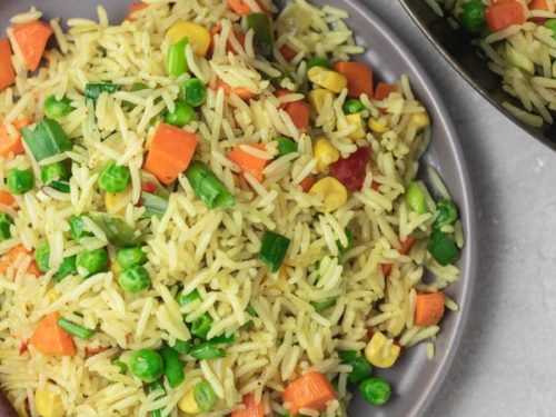 a plate of vegetable fried rice and wok on the side.