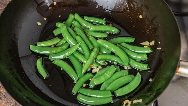 sauteing snap peas in wok.