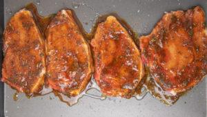 marinated pork chops on a baking tray.