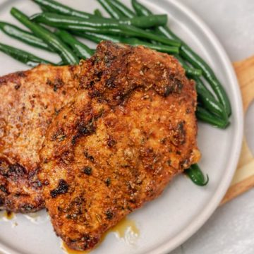 a plate of pork chops and green beans.