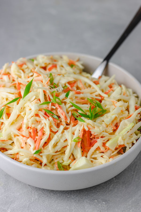 a bowl of cabbage garnished with chopped green onions.