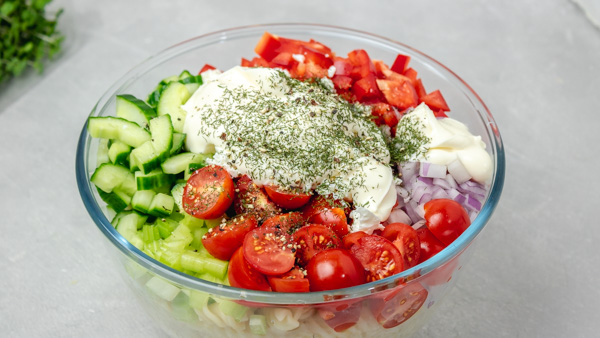 a bowl of freshly chopped vegetable with mayonnaise and herbs.