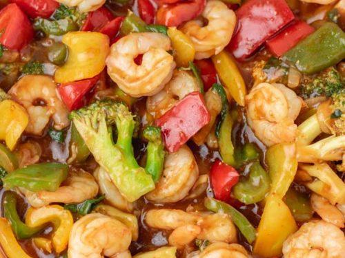 a skillet of shrimp stir fry and vegetables.
