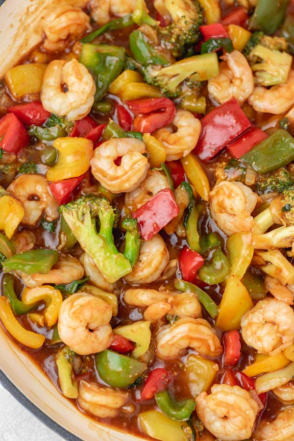 a skillet of shrimp stir fry and vegetables.