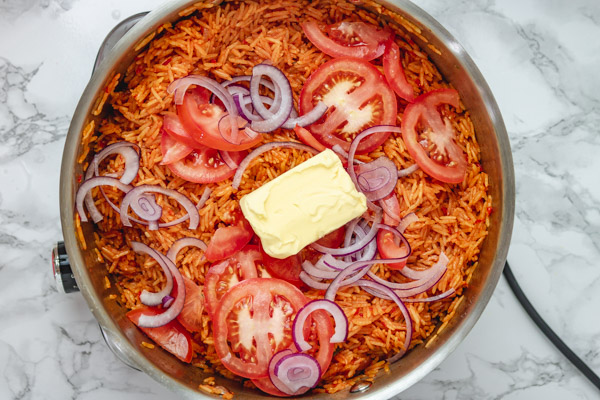sliced tomatoes. onions and butter on rice in a pot.
