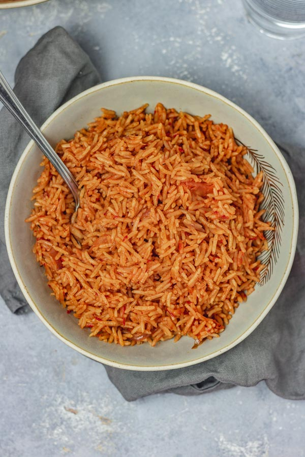 a plate of jollof rice placed on a grey napkin.